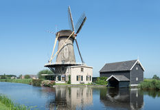 Dutch windmill at a canal on a sunny summer day Royalty Free Stock Photos