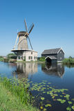 Dutch windmill at a canal on a sunny summer day Stock Photos