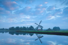Dutch windmill close to river during calm sunrise Royalty Free Stock Images