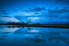 Dutch windmill and clouds in dusk. Reflected in river, Holland Stock Photo