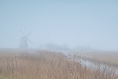 Dutch windmill in dense fog Stock Photos