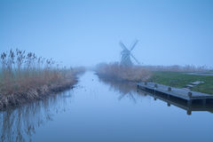 Dutch windmill in dense fog by river Royalty Free Stock Images