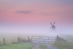 Dutch windmill in dense fog at sunrise Stock Photo