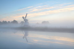 Dutch windmill in dense fog during sunrise Stock Image