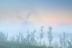 Dutch windmill in dense sunrise fog Royalty Free Stock Photos
