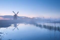 Dutch windmill in dense sunrise mist Royalty Free Stock Image