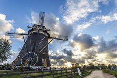 Dutch windmill. At and facing the sunset with dramatics clouds and shiny sunset landscape Royalty Free Stock Images