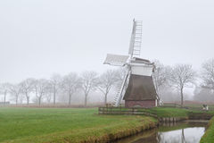 Dutch windmill in fog Royalty Free Stock Image