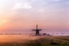 Dutch windmill in fog in the early morning Stock Photography