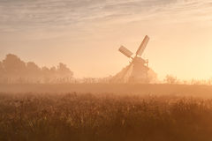 Dutch windmill in fog and morning sunshine Royalty Free Stock Image