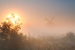 Dutch windmill in fog at sunrise royalty free stock image