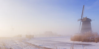 Dutch windmill in a foggy winter landscape in the morning Royalty Free Stock Photo