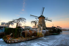 Dutch windmill with garden in the sunset. Dutch windmill with a nice garden in the sunset in wintertime Royalty Free Stock Images