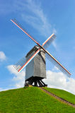 Dutch windmill on green hill with blue sky Royalty Free Stock Images