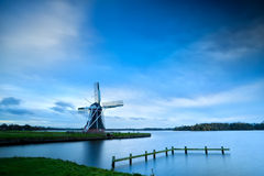 Dutch windmill by lake with long exposure Royalty Free Stock Image