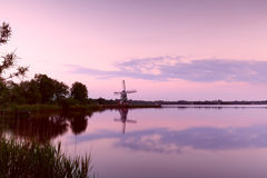 Dutch windmill at sunset. Dutch windmill by lake at sunset, Groningen Stock Images