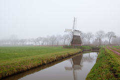 Dutch windmill in misty day Royalty Free Stock Image