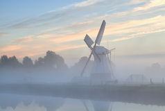 Dutch windmill in morning fog at sunrise Stock Photo