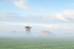 Dutch windmill in morning fog Royalty Free Stock Photography