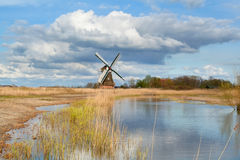 Dutch windmill over blue sky by river Royalty Free Stock Images