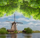 Dutch windmill over  river waters Royalty Free Stock Photo
