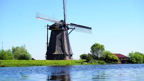 Dutch windmill over river waters. Traditional dutch windmill , Kinderdijk at summer day, Netherland stock video footage