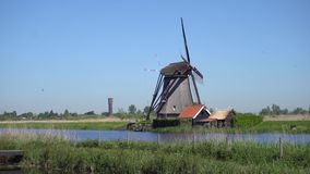 Dutch windmill over river waters. Traditional dutch windmills site with flying birds, Kinderdijk at summer day, Netherland stock footage