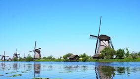 Dutch windmill over river waters. Traditional dutch windmills site with boat passing by Kinderdijk at summer day, Netherland stock video footage