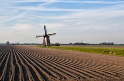 Dutch windmill by plowed field Stock Images