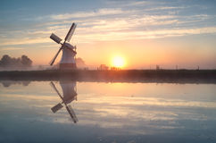 Dutch windmill reflected in river at sunrise Royalty Free Stock Photo
