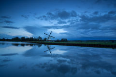 Dutch windmill by river in dusk Royalty Free Stock Images