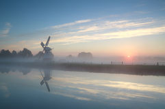 Dutch windmill by river during misty sunrise Stock Photography