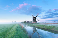 Dutch windmill by river at sunrise Royalty Free Stock Photos