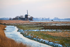 Dutch windmill by river in winter Royalty Free Stock Photos