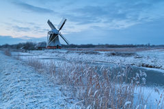 Dutch windmill by river in winter Stock Image