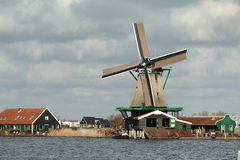 Dutch windmill on the side of the river. Scenery depicting typical dutch landscape Royalty Free Stock Images