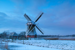 Dutch windmill in snow at sunrise Stock Photos