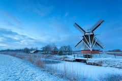 Dutch windmill on snow in winter dusk Royalty Free Stock Image