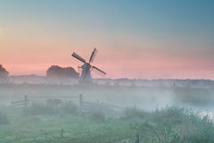 Dutch windmill in summer morning fog Stock Image