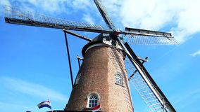 Dutch Windmill on Sunny Day. A Dutch windmill turns on a sunny day in the province of Zeeland with Dutch flags flying stock footage