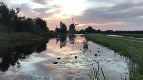 Dutch windmill sunrise water refection. Dutch warm and vivid sunrise landscape in the Hazerswoude city, Netherlands stock video