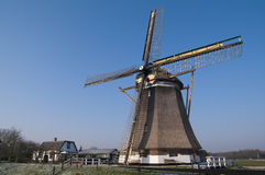 Dutch windmill in the winter. On a green dyke covered with hoarfrost Stock Photo