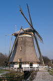 Dutch windmill in the winter. On a green dike covered with hoarfrost Stock Photo