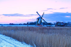 Dutch windmill in winter at sunrise Stock Photos