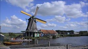 Dutch windmill working on canal at Zaanse Schans, Holland stock video