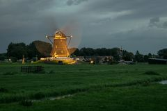Dutch windmill is working and illuminated by lights at blue hour royalty free stock photography