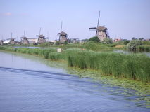 Dutch windmills along canal Royalty Free Stock Images