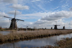 Dutch windmills landscape. Group of windmills under bright blue skies, watermills, Netherlands, Holland, crisp day, water landscape, farm landscape Stock Photo