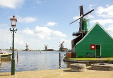 Dutch windmills over river in Zaanse Schans Royalty Free Stock Images
