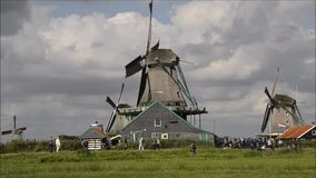Dutch windmills turning on canal at Zaanse Schans, Holland stock video